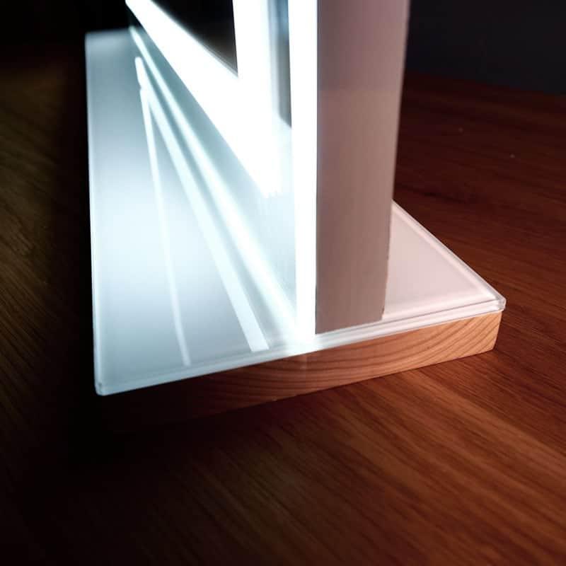กระจกแต่งหน้ามีไฟวางบนโต๊ะ